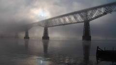 Sun burns through fog near railroad bridge Stock Footage