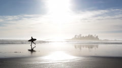 Stock Video Footage of Surfer runs across beach.