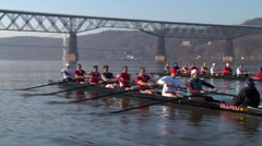 A crew boat team rows with bridge in background Stock Footage