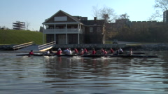 Two crew boats race past boathouse - stock footage