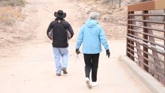 Retired Couple walks thru park Stock Footage