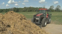 Tractor turning manure pile 02 Stock Footage
