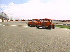 Motorsports, legend race cars pass by camera low Stock Footage
