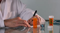 pharmacist pouring pills into bottle - stock footage