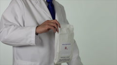 Pharmacist putting drugs in bag Stock Footage