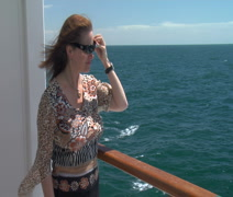 Woman enjoys ocean view and breeze from cruise ship balcony Stock Footage