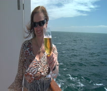 Woman on cruise ship balcony toasts champaign to camera Stock Footage