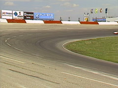 Motorsports, IMCA modifieds stock car race in corner through frame, wide shot Stock Footage