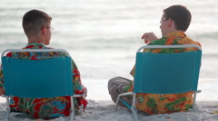 Brothers talking on the beach Stock Footage