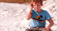 Stock Video Footage of Young boy listens to ocean in seashell