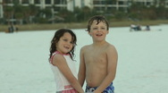 Little boy and girl enjoying sunset at beach Stock Footage