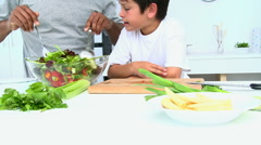 Boy cooking a salad with his father Stock Footage