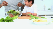 Stock Video Footage of Boy cooking a salad with his father