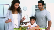 Woman cooking a salad with her son Stock Footage