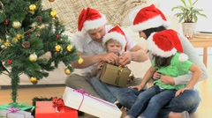Joyful family opening Christmas gift Stock Footage