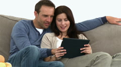 Couple using a computer tablet sitting on the sofa Stock Footage