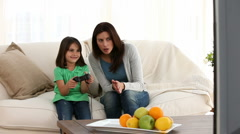 Cheerful mom encouraging her daughter to play video games Stock Footage