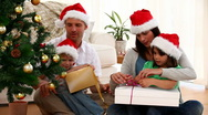 Happy family opening a christmas present at home Stock Footage
