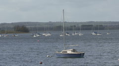 Yacht moored to buoy turns on wind on Rutland Water. - stock footage