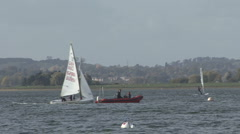 Sail training - dinghy does loops around a RIB on Rutland Water. Stock Footage