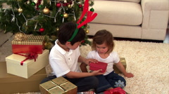 Montage of two children opening their present - stock footage