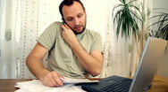 Man in home office with computer, phone and paperwork Stock Footage