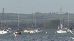 A motorboat passes yachts moored to buoys on Rutland Water. - stock footage