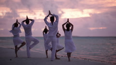 Family of six doing yoga at sunset on a beach Stock Footage