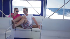 young couple sitting close in speed boat - stock footage