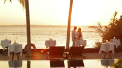 Couple at tropical sunset with drinks Stock Footage