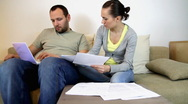 Stock Video Footage of Couple sitting on sofa at home and calculating bills