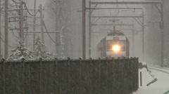 Train under snow storm arrives at train station Stock Footage