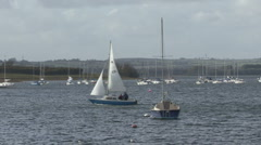 Small yacht passes another yacht moored to a buoy on Rutland Water. - stock footage