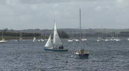 Small yacht passes another yacht moored to a buoy on Rutland Water. Stock Footage