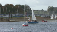 Small yacht passes through frame R-L on Rutland Water. - stock footage