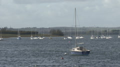 Yacht moored to a buoy turns on wind on Rutland Water. - stock footage