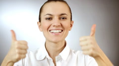Woman gesturing a thumbs up sign, grey background  - stock footage