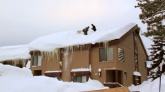 SHOVELING SNOW OFF A ROOF Stock Footage