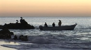 Stock Video Footage of Sunrise Fishermen In Small Boat Near Shore With Pelicans