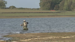 Angler standing at the edge of Rutland Water casts. - stock footage