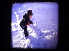 Cute little boy digs in snow Stock Footage