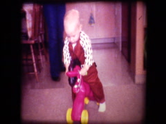 Cute little blonde boy rides toy horse smiles at camera Stock Footage
