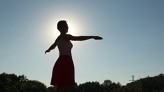 silhouette of woman rotating against sky - stock footage