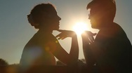 Silhouettes of couple sits on bench and talks Stock Footage