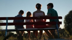 family of four sits on bench in park - stock footage