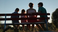 Family of four sits on bench in park Stock Footage