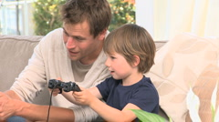 Son and dad playing video games Stock Footage