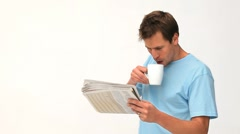Man drinking a coffee while he is reading a newspaper Stock Footage