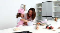 Girl baking biscuits with her mother - stock footage