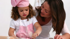 Attentive mother helping her daughter to bake - stock footage